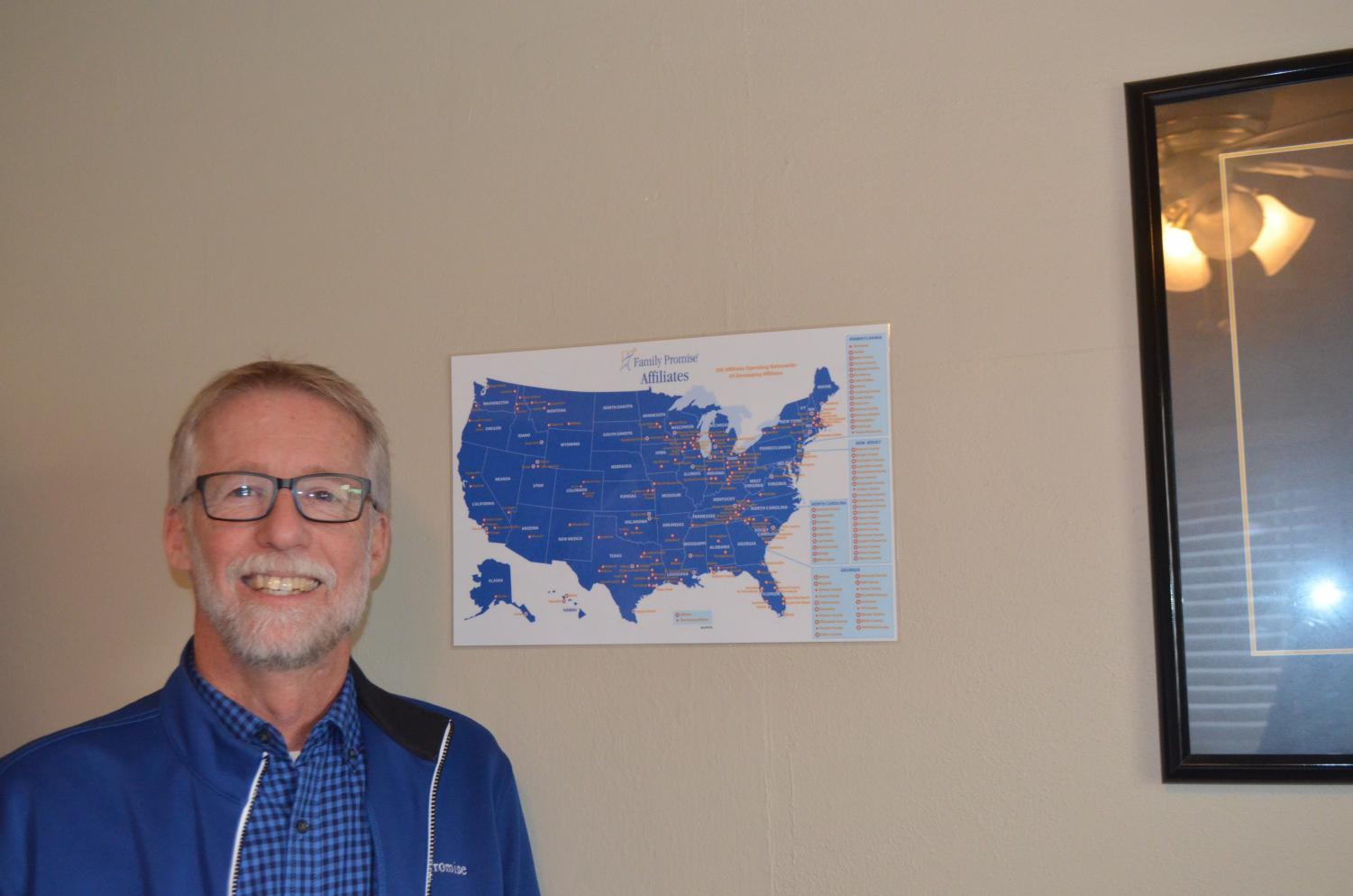 Steve Thomas, the executive director of Family Promise posing next to a map that marks all of the other Family Promise branches. Photo by Loretta Tuell.