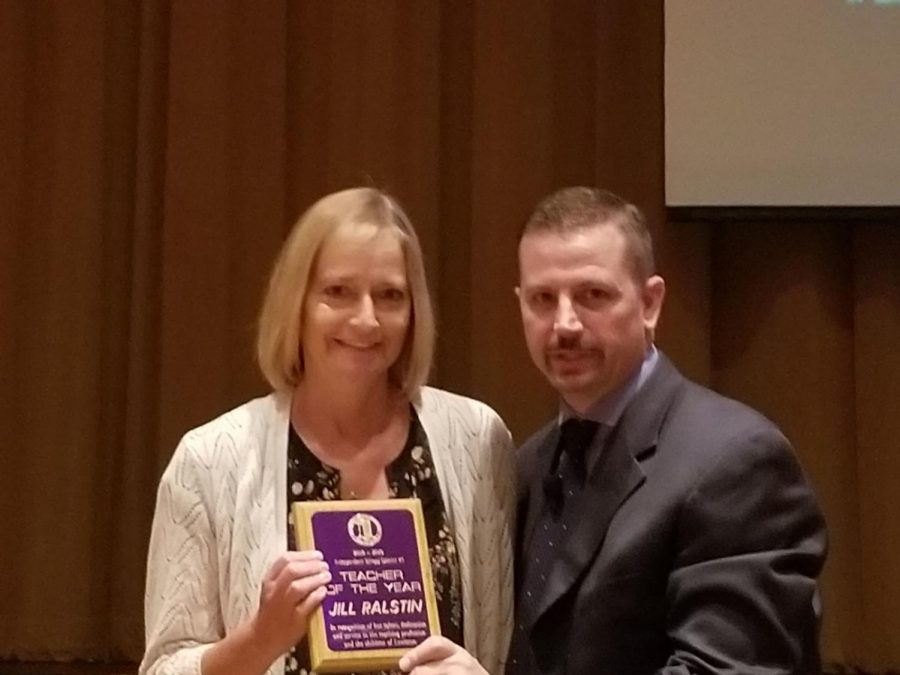 Jill Ralstin (left) receives Teacher of the Year in August 2018 from Lance Hansen (right), assistant superintendent.