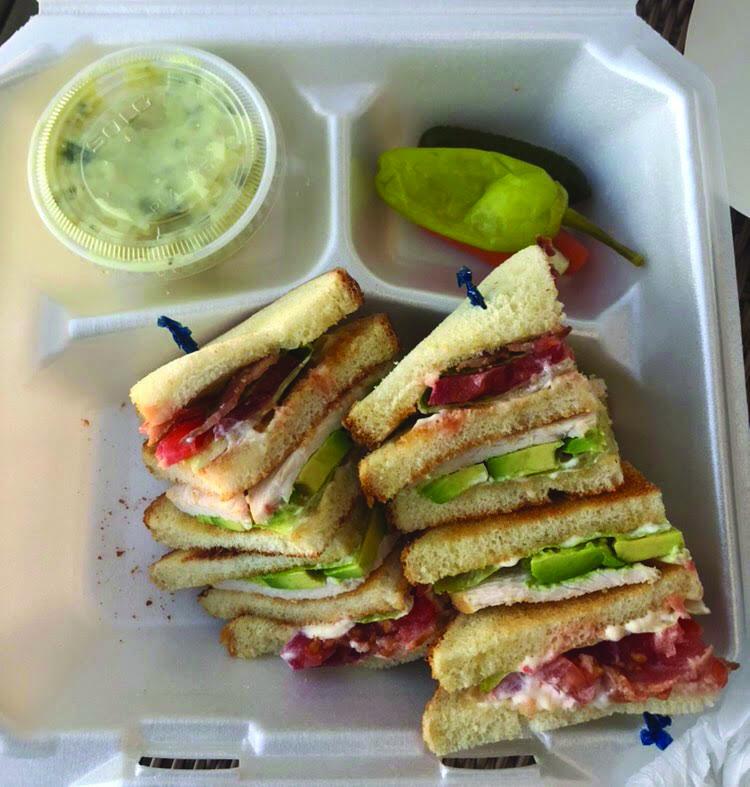 The+Turkey+Bacon+Avocado+Triple+Decker+Club+prepares+to+be+eaten.+
