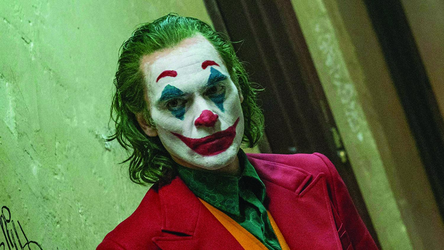 Arthur Fleck sports his new look as Joker, with dyed green hair, his face made up like a clown, and a colorful suit to match. Photo courtesy of IMDb.