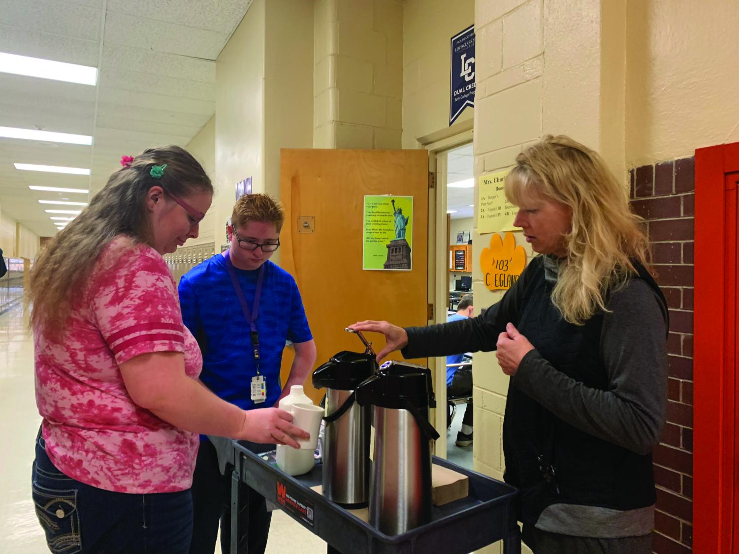 Two Life Skills students (left) help prepare coffee for a teacher as a part of the new coffee cart service. Photo by Kim Neri.