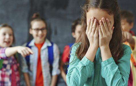 Girl cries as classmates bully her. Photo courtesy of Getty Images.