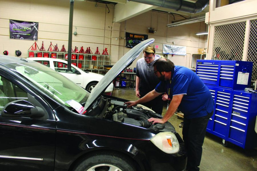 Steve Hoffine teaches a student about the care and internal working of a car.