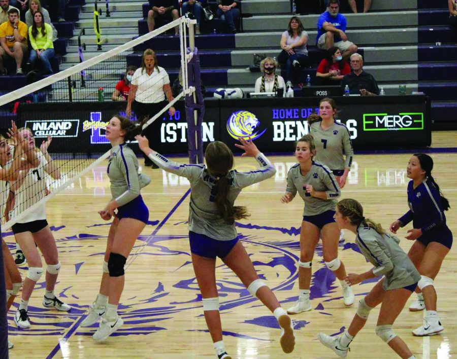 Kylee Estlund soars through the air, spiking a ball over the net.